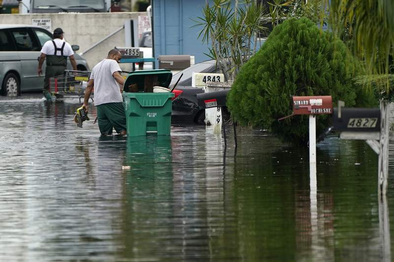 Residents clear debris from a flooded street in the Driftwood Acres Mobile Home Park, in the aftermath of Tropical Storm Eta, Tuesday, Nov. 10, 2020, in Davie, Fla. Tropical Storm Eta was squatting off western Cuba on Tuesday after drifting away from South Florida, where it unleashed a deluge that flooded entire neighborhoods and covered the floors of some homes and businesses. (AP Photo/Lynne Sladky)