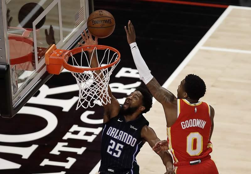 Orlando Magic guard Chasson Randle (25) lays up a shot past Atlanta Hawks' Brandon Goodwin, right, during the first half of an NBA basketball game Tuesday, April 20, 2021, in Atlanta. (AP Photo/Ben Margot)