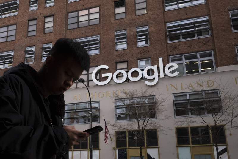 FILE - In this file photo dated Monday, Dec. 17, 2018, a man using a mobile phone walks past Google offices in New York. Google is planning to buy New York's St.  Johns Terminal for $2.1 billion, making it the anchor of its Hudson Square campus.  Alphabet and Google Chief Financial Officer Ruth Porat said Tuesday, Sept. 21, 2021,  that the company is looking to invest more than $250 million in its New York campus this year. (AP Photo/Mark Lennihan, FILE)