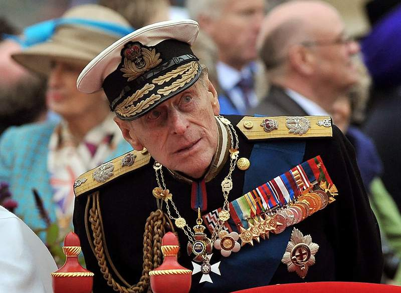 """FILE - A Sunday June 3, 2012 photo from files showing Prince Philip watching the proceedings from the royal barge during the Diamond Jubilee Pageant on the River Thames in London. Buckingham Palace said Thursday March 4, 2021, that Prince Philip has undergone a successful procedure for a pre-existing heart condition, and will remain in hospital """"for a number of days."""" (AP Photo/John Stillwell, Pool File)"""