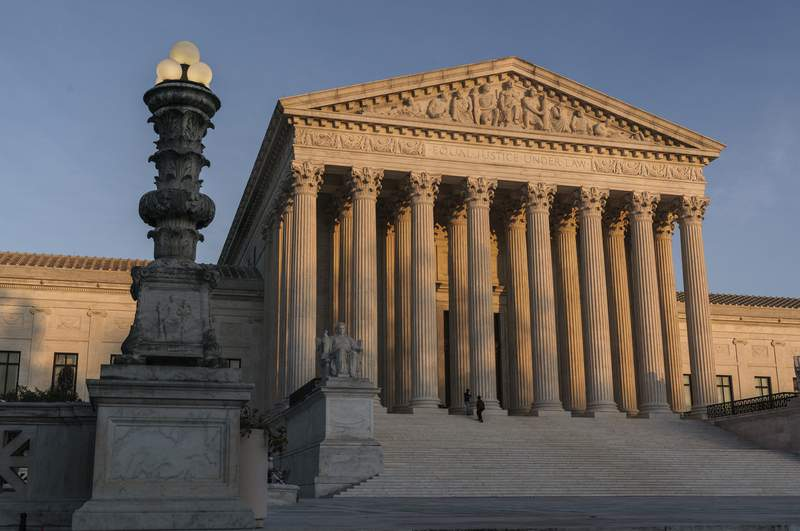 FILE - In this Nov. 6, 2020, file photo the Supreme Court is seen as sundown in Washington. The Supreme Court says it will continue to hear arguments by telephone through at least January because of the coronavirus pandemic. The courts announcement Wednesday, Nov. 25, extends telephone arguments by a month. (AP Photo/J. Scott Applewhite, File)