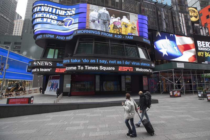 A couple looks at the ABC News video screen showing coverage of a coronavirus outbreak in Woodbridge, N.J., Wednesday, March 25, 2020, in New York's Times Square. The number of people hospitalized with COVID-19 in New York climbed to 3,800, with close to 900 in intensive care, with the peak of the outbreak weeks away, Gov. Andrew Cuomo said Wednesday. The new coronavirus causes mild or moderate symptoms for most people, but for some, especially older adults and people with existing health problems, it can cause more severe illness or death. (AP Photo/Mary Altaffer)
