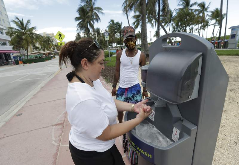 Maria Gomez, foreground, washes her hands at a portable hand washing station as she and Barry Molett, back, enjoy a day on Miami Beach, Florida's famed South Beach, Monday, June 22, 2020. More than 100,000 people in Florida have been diagnosed with the coronavirus, state health officials reported Monday, as public health officials reissued advisories urging social distancing and mask wearing. (AP Photo/Wilfredo Lee)