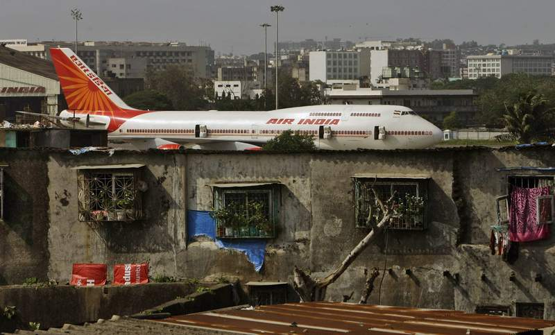 FILE- In this May 25, 2010 file photo, an Air India plane is seen in the background of slums adjoining the the international airport in Mumbai, India. Personal data of an unspecified number of travelers has been comprised in a hack of a company that manages customer data including credit cards, passports and phone numbers for Indias national carrier. The hackers were able to access ten years worth of data from the Atlanta-based SITA Passenger Service System that serves Air India, the airline said in a statement Friday. (AP Photo/Rajanish Kakade, file)