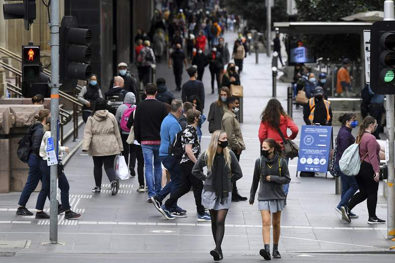 People wearing face mask walk along Bourke Street Mall in Melbourne, Friday, Nov. 6, 2020. Australias highest court on Friday upheld a states border closure and dismissed billionaire businessman Clive Palmers argument that the pandemic measure was unconstitutional.(James Ross/AAP Images via AP)