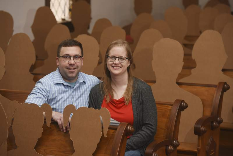 Dan Stuglik and Amy Simonson are photographed Tuesday, March 31, 2020 in Pokagon, Mich. The two will be joined by more than 100 cardboard cutouts of family and friends when they are married this Saturday at The Old Rugged Cross Church in Pokagon. The COVID-19 pandemic has forced the couple to change their original plan of inviting 150 people to one where only a handful will be present, but with the help and donation of the cutouts by Menasha Packaging, the two will be able to fill the pews.(Don Campbell/The Herald-Palladium via AP)