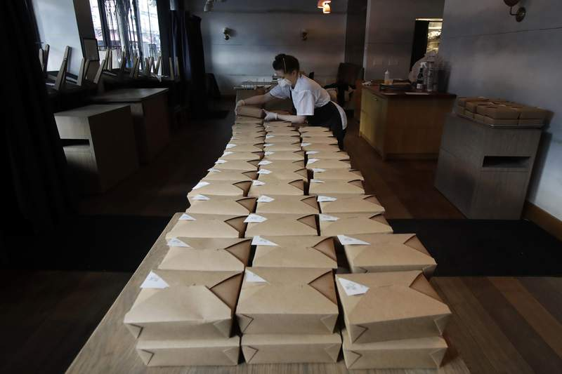 """FILE - In this Friday, March 27, 2020, file photo, Nightbird Restaurant pastry chef Hope Waggoner prepares dinner boxes that were to be delivered to hospital workers in San Francisco. California Gov. Gavin Newsom announced Friday, April 24 that taxpayers will pay restaurants to make meals for millions of California's seniors during the coronavirus pandemic, an initiative that could pump billions of dollars into a devastated industry. Nightbird owner Kim Alter said in an email that the restaurant is """"working to be a part of this."""" (AP Photo/Jeff Chiu, File)"""