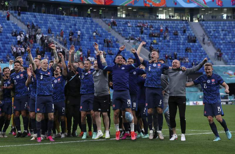 Slovakian players celebrate at the end of the Euro 2020 soccer championship group E match between Poland v Slovakia at the Saint Petersburg stadium in St. Petersburg, Russia, Monday, June 14, 2021. (Evgenya Novozhenina/Poolvia AP)