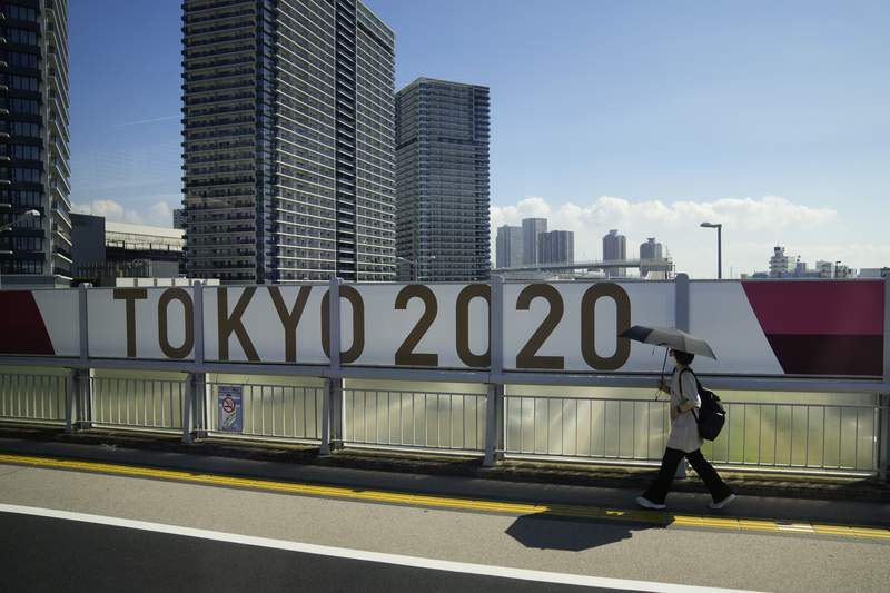 A woman walks on a bridge past a Tokyo 2020 banner ahead of the 2020 Summer Olympics, Saturday, July 17, 2021, in Tokyo. Tokyo is under a fourth state of emergency, which began Monday and requires restaurants and bars to close early and not serve alcohol through the games, which start July 23. (AP Photo/Jae C. Hong)