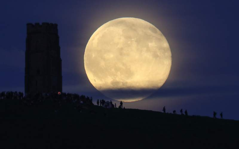 A full moon rises behind Glastonbury Tor as people gather to celebrate the summer solstice on June 20 in Somerset, England.