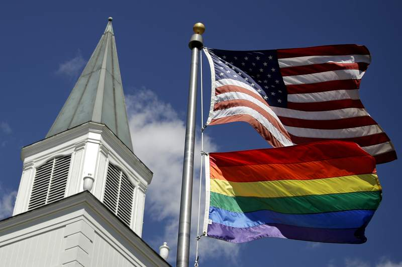 FILE - In this April 19, 2019 file photo, a gay pride rainbow flag flies along with the U.S. flag in front of the Asbury United Methodist Church in Prairie Village, Kan. Conservative leaders within the United Methodist Church unveiled plans Monday, March 1, 2021 to form a new denomination, the Global Methodist Church, with a doctrine that does not recognize same-sex marriage. The move could hasten the long-expected breakup of the UMC, Americas largest mainline Protestant denomination, over differing approaches to LGBTQ inclusion. (AP Photo/Charlie Riedel, File)