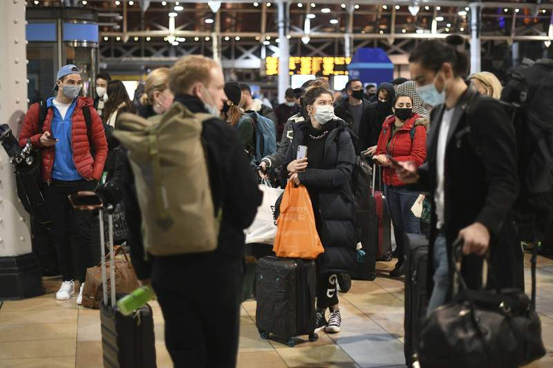 People wait on the concourse at Paddington Station in London, on the last Saturday shopping day before Christmas, after the announcement that London will move into Tier 4 COVID-19 restrictions from midnight, Saturday Dec. 19, 2020. (Stefan Rousseau/PA via AP)