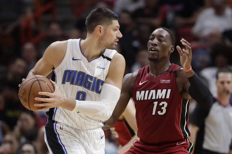 Orlando Magic center Nikola Vucevic (9) looks for an opening past Miami Heat forward Bam Adebayo (13) during the first half of an NBA basketball game Wednesday, March 4, 2020, in Miami. (AP Photo/Wilfredo Lee)