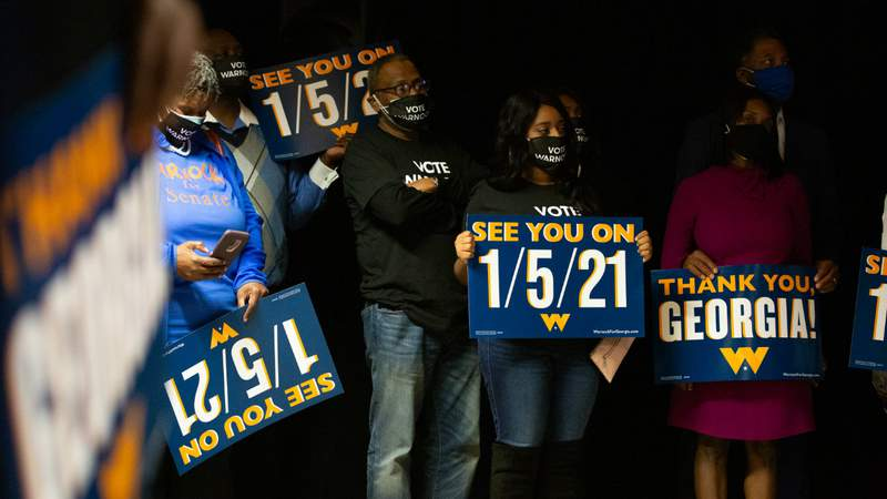 Family and supporters hold runoff signs as Democratic U.S. Senate candidate Rev. Raphael Warnock speaks during an Election Night event on November 3, 2020 in Atlanta, Georgia. Warnock is running in a special election on Jan. 5. against U.S. Sen. Kelly Loeffler. Photo by Jessica McGowan