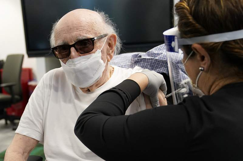 Dr. Norman G. Einspruch, 88, receives the Pfizer-BioNTech COVID-19 vaccine at Jackson Memorial Hospital, Wednesday, Dec. 30, 2020, in Miami. Jackson Health System is starting to vaccinate people over the age of 65 this week. (AP Photo/Lynne Sladky)