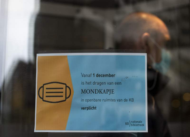 A man entering the national library in The Hague, Netherlands, Tuesday, Dec. 1, 2020, passes a sign informing visitors to wear mandatory face masks. Wearing face masks in publicly accessible indoor venues such as libraries, museums became obligatory in the Netherlands on Dec. 1, 2020, when a new temporary law underpinning existing government coronavirus restrictions came into force. (AP Photo/Peter Dejong)