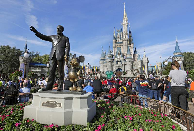 FILE - In this Jan. 9, 2019, file photo, guests watch a show near a statue of Walt Disney and Micky Mouse in front of the Cinderella Castle at the Magic Kingdom at Walt Disney World in Lake Buena Vista, Fla. The Walt Disney Co.'s net income fell sharply in its most-recent quarter, as the coronavirus pandemic still weighs heavily on many of its businesses, from theme parks to movies, the company announced Thursday, Feb. 11, 2021. (AP Photo/John Raoux, File)