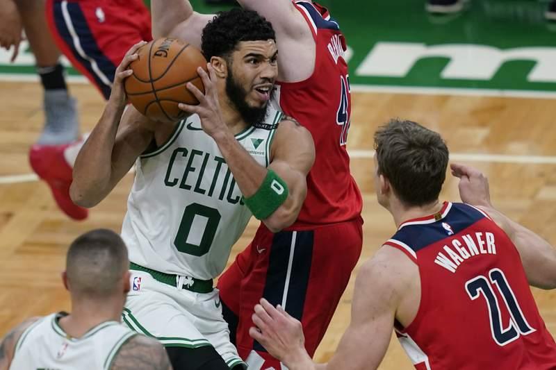 Boston Celtics forward Jayson Tatum (0) drives against Washington Wizards' Davis Bertans and center Moritz Wagner (21) in the second half of an NBA basketball game, Friday, Jan. 8, 2021, in Boston. (AP Photo/Elise Amendola)