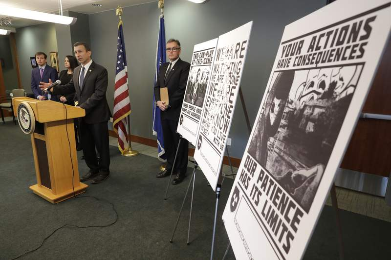 FILE - In this Feb. 26, 2020, file photo, Raymond Duda, FBI Special Agent in Charge in Seattle, speaks during a news conference at a podium, about charges against a group of alleged members of the neo-Nazi group Atomwaffen Division for cyber-stalking and mailing threatening communications, including the Swastika-laden posters at right, in a campaign against journalists in several cities. Johnny Roman Garza, an Arizona man has been sentenced to 16 months in prison for his role in a neo-Nazi group's coordinated campaign to threaten and harass journalists, activists and other targets on both U.S. coasts, Wednesday, Dec. 9, 2020.  (AP Photo/Ted S. Warren, File)