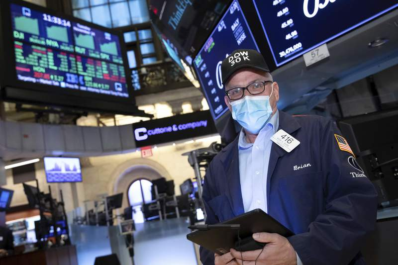 A trader works at the New York Stock Exchange, Tuesday, November 24, 2020. The Dow Jones Industrial Average traded above 30,000 points for the first time as investors were encouraged by the latest progress on developing coronavirus vaccines and news that the transition of power in the U.S. to President-elect Joe Biden will finally begin. (Nicole Pereira/NYSE via AP)