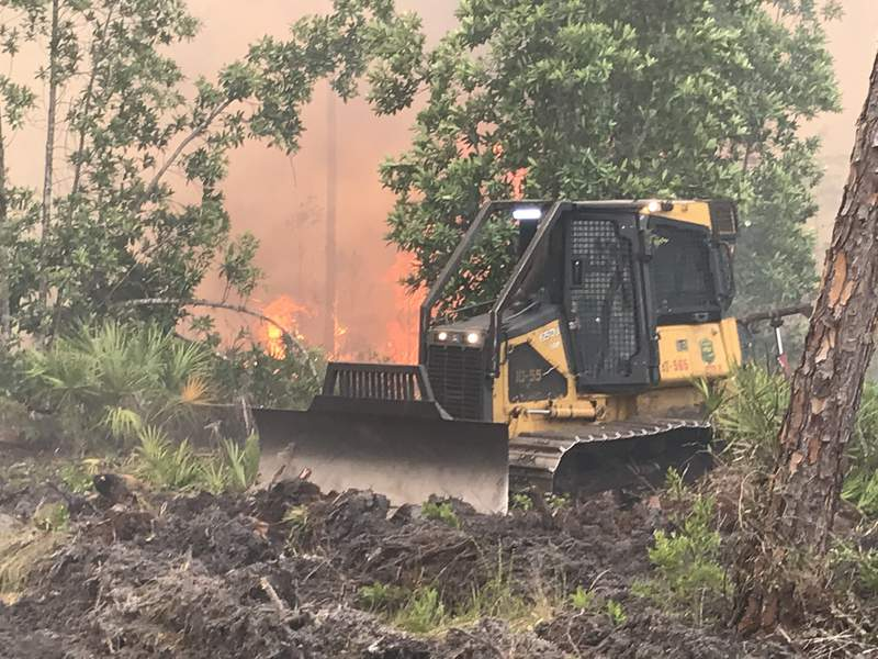 A bulldozer working to contain a 1,000-acre brush fire in Volusia County on June 12, 2021. (Image: Florida Fire Service)