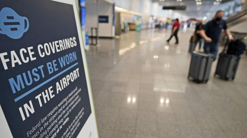 A sign requiring masks is displayed as travelers move about at Cleveland Hopkins International Airport, Wednesday, May 26, 2021, in Cleveland. (AP Photo/Tony Dejak)