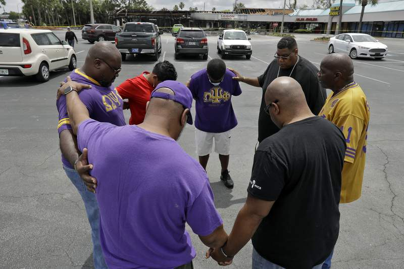 Members of the Omega Psi Phi fraternity hold hands in prayer in the parking lot Monday, June 1, 2020, in Tampa, Fla., near where two places of business were destroyed by protesters Saturday night. Several counties across Florida issued curfews to curb large crowds gathering to protest the killings of black people by police. (AP Photo/Chris O'Meara)
