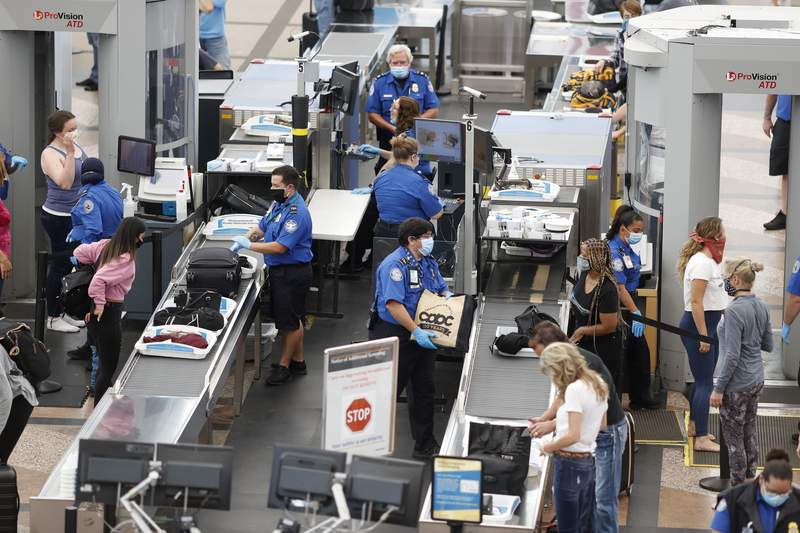 FILE - In this June 10, 2020 file photo, Transportation Security Administration agents process passengers at the south security checkpoint at Denver International Airport in Denver. Federal safety officials are investigating people who took part in last week's riot at the U.S. Capitol to decide whether they belong on the federal no-fly list. The move is one of several that officials outlined Friday, Jan. 15, 2021.  (AP Photo/David Zalubowski, File)