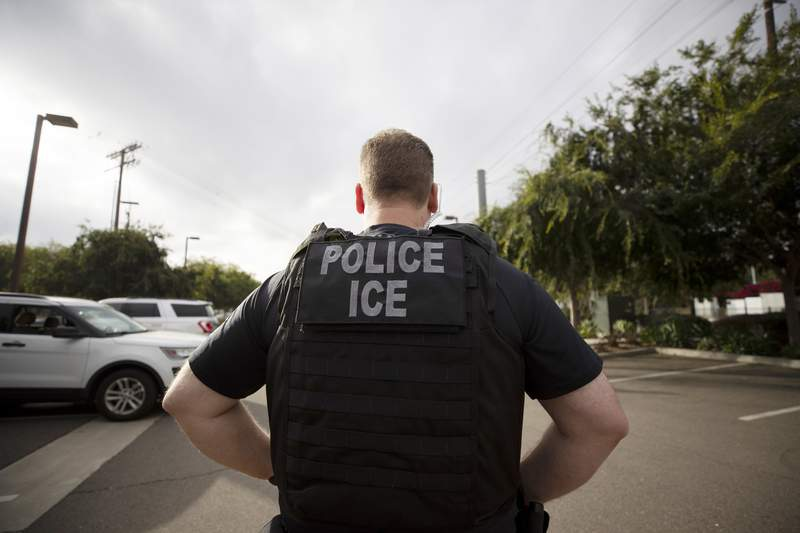 FILE - In this July 8, 2019, file photo, a U.S. Immigration and Customs Enforcement (ICE) officer looks on during an operation in Escondido, Calif.  Pressure is mounting on the Trump administration to release people from immigration detention facilities where at least one detainee has already tested positive for COVID-19.  (AP Photo/Gregory Bull, File)