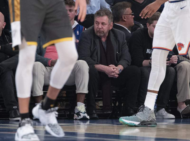 FILE - In this March 6, 2020, file photo, New York Knicks owner James Dolan, center, watches the first half of an NBA basketball game between the Knicks and the Oklahoma City Thunder at Madison Square Garden in New York. Dolan, the executive chairman of Madison Square Garden Company and owner of the Knicks, has tested positive for the coronavirus. The Knicks announced Dolans diagnosis Saturday night, March 28. It is not clear when he was tested or when he received the diagnosis. (AP Photo/Mary Altaffer, File)