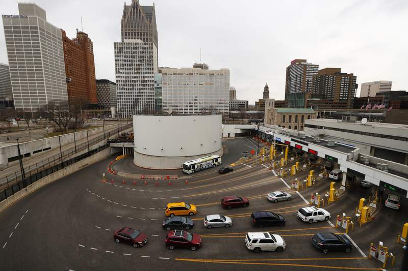 Vehicles enter the United States as a bus drives to Canada in the Detroit-Windsor Tunnel in Detroit, Monday, March 16, 2020. Canadian Prime Minister Justin Trudeau says he is closing his country's borders to anyone not a citizen, an American or a permanent resident amid the coronavirus outbreak. (AP Photo/Paul Sancya)