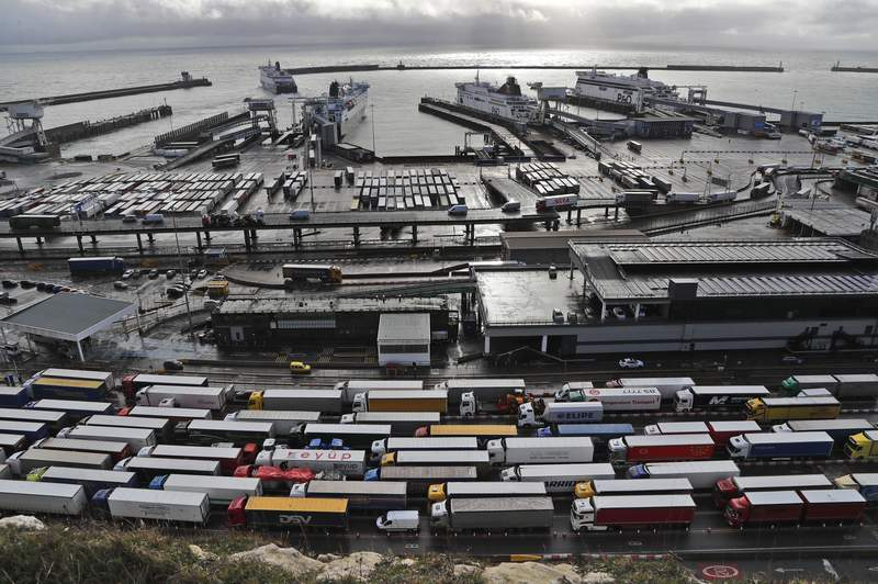 FILE - In this Friday, Dec. 11, 2020 file photo, lorries queue at Check-in at the port in Dover, Britain, before entering the EU. Britain announced Thursday, March 11, 2021 that it is delaying the imposition of checks on some goods from the European Union to give businesses more time to prepare for new post-Brexit rules. The U.K. government says it is postponing full border controls until Jan. 1, six months later than planned, because of disruption caused by the coronavirus pandemic. (AP Photo/Frank Augstein, file)