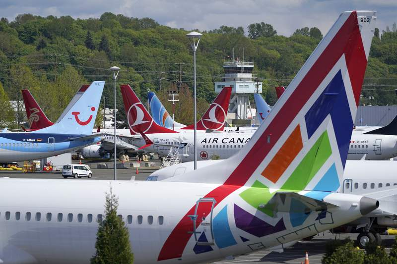 FILE  In this April 26, 2021, file photo Boeing 737 Max airplanes sit parked in a storage lot, near Boeing Field in Seattle. The Boeing Co. told employees, Tuesday, Oct. 12, 2021, that they must be vaccinated against COVID-19 or possibly be fired. The Seattle Times reports the deadline for workers at the aerospace giant is Dec. 8. (AP Photo/Ted S. Warren, File)