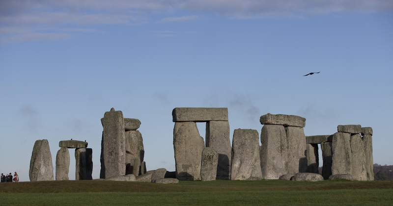 FILE - In this Tuesday, Dec. 17, 2013 file photo, visitors take photographs of the world heritage site of Stonehenge, in Wiltshire England. The prehistoric monument of Stonehenge in southern England was closed to visitors Saturday, Dec. 5, 2020, in the afternoon after protesters staged a mass trespass against the British governments road-building plans, which includes a new tunnel near the World Heritage Site. The protesters, who described themselves as an alliance of local residents, ecologists, activists, archaeologists and pagans, gathered at Stonehenge around midday.  (AP Photo/Alastair Grant, File)