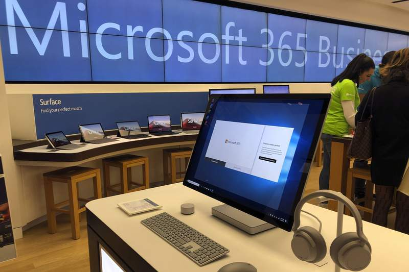 FILE - In this Jan. 28, 2020 file photo a Microsoft computer is among items displayed at a Microsoft store in suburban Boston.   A tool designed to help businesses protect themselves from further compromises after a global hack of Microsoft email server software has been downloaded more than 25,000 times since it was released last week. That's according to the White Houses National Security Council. As a result, the number of vulnerable systems has fallen by 45 percent.  (AP Photo/Steven Senne, File