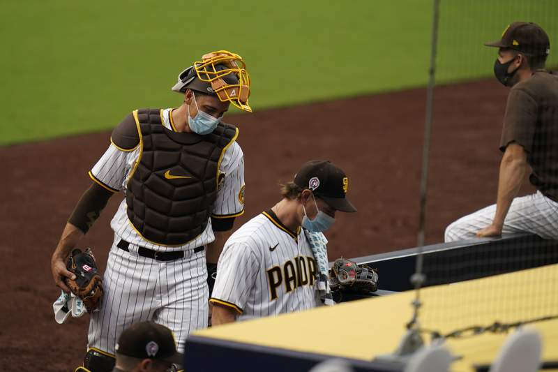 San Diego Padres starting pitcher Garrett Richards, center, walks into the dugout followed by catcher Austin Nola after the team's baseball game against the San Francisco Giants was postponed Friday, Sept. 11, 2020, in San Diego, minutes before the scheduled first pitch after someone in the Giants organization tested positive for COVID-19. (AP Photo/Gregory Bull)