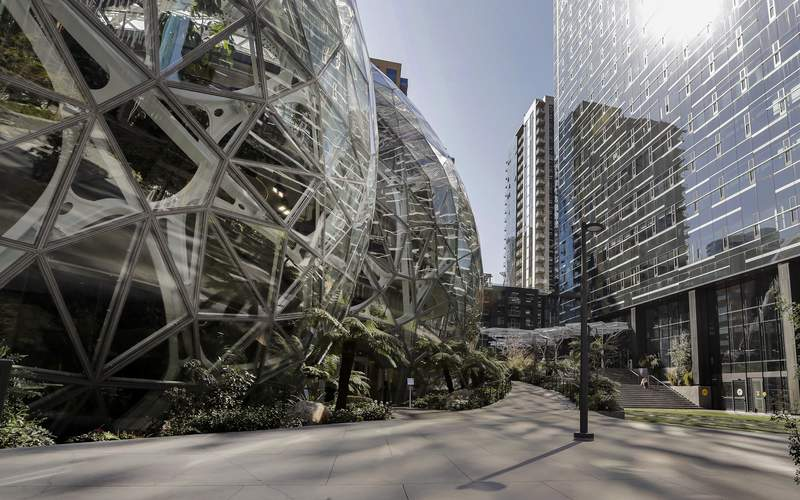 FILE - In this March 20, 2020, file photo, the Amazon campus outside the company headquarters in Seattle sits nearly deserted on an otherwise sunny and warm afternoon. Amazon said Monday, Oct. 11, 2021 it will allow many tech and corporate workers to continue working remotely indefinitely, as long as they can commute to the office when necessary. (AP Photo/Elaine Thompson, File)
