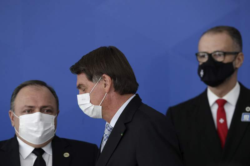Brazilian President Jair Bolsonaro walks past his Health Minister Eduardo Pazuello, left, and President of the Sanitary Agency Antonio Barra Torres before a ceremony to sign a law that expands the federal government's ability to acquire COVID-19 vaccines, at Planalto presidential palace in Brasilia, Brazil, Wednesday, March 10, 2021. (AP Photo/Eraldo Peres)