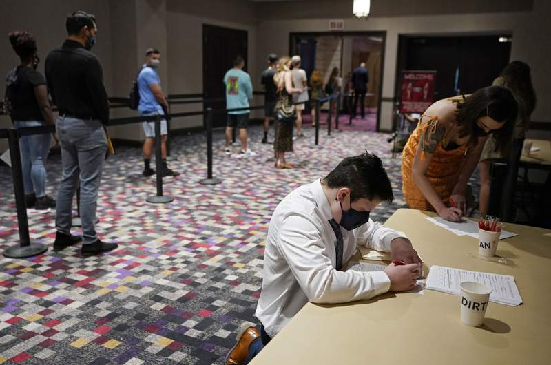 FILE - In this April 22, 2021, file photo, people wait in line to apply for seasonal jobs at Virgin Hotels Las Vegas in Las Vegas. The hotel-casino, which opened in March, held the casting call to hire for seasonal positions at the resort pool and dayclub. Hotels, restaurants and other businesses in tourist destinations are warning that hiring challenges during the coronavirus pandemic could force them to pare back operating hours or curtail services just as theyre eyeing a bounce-back summer. (AP Photo/John Locher, File)