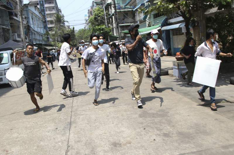 Anti-coup protesters run to avoid military forces during a demonstration in Yangon, Myanmar on Wednesday March 31, 2021. The Southeast Asian nation has been wracked by violence since the military ousted a civilian-led government on Feb. 1 and began to forcibly put down protests. (AP Photo)