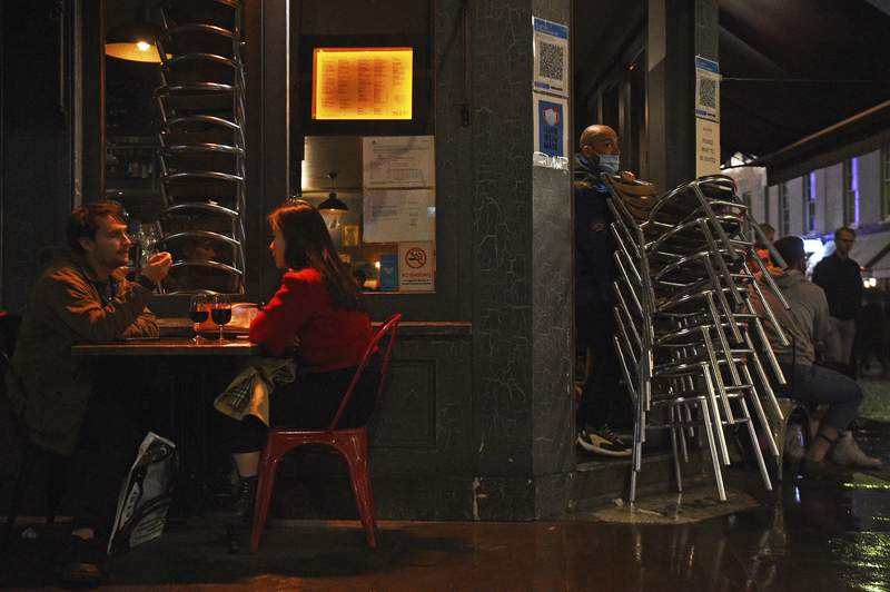 A worker packs away chairs outside a bar in Soho, London, ahead of the 10pm curfew pubs and restaurants are subject to in order to combat the rise in coronavirus cases in England, Friday, Oct. 2, 2020. (Kirsty O'Connor/PA via AP)