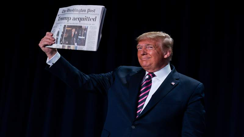 "President Donald Trump holds up a newspaper with the headline that reads ""Trump acquitted"" during the 68th annual National Prayer Breakfast, at the Washington Hilton, Feb. 6, 2020, in Washington."