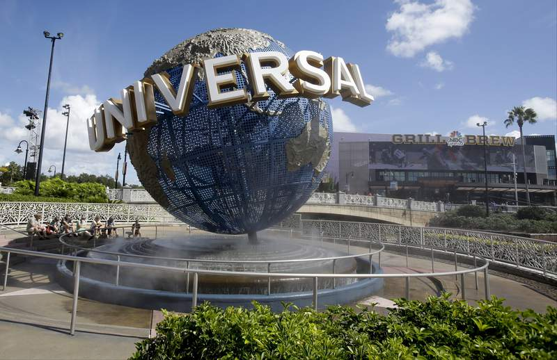 """FILE - In this Thursday, Oct. 22, 2015, file photo, park guests relax and cool off with a water mist under the globe at Universal Studios City Walk in Orlando, Fla. Florida tourism officials say cases of the new coronavirus are having little visible impact on the state's biggest industry so far. Tom Schroder, a spokesman for Universal Orlando, said it is reinforcing """"best-practice health and hygiene procedures"""" in response to the coronavirus outbreak and adding more hand sanitizer units to its parks. (AP Photo/John Raoux, File)"""