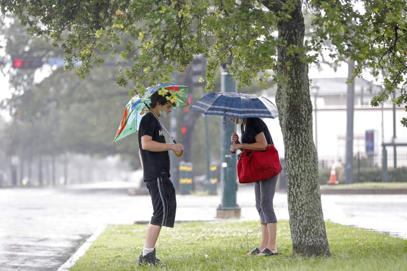 Keller Bell, left, and his mother Sheri Bell shelter from the rain under a tree and umbrellas as they wait for a bus in advance of Tropical Storm Cristobal in New Orleans, Sunday, June 7, 2020. (AP Photo/Gerald Herbert)