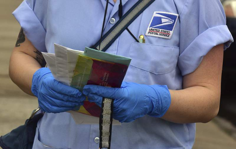 FILE - In this Friday March 20, 2020 file photo, a U.S Postal Service mail carrier wears gloves while delivering mail in South Wilkes-Barre, Pa. Health experts say the risks are very low that coronavirus will remain on envelopes or packages and infect anyone that comes in contact with it. But those on the frontlines of all those deliveries are taking steps to try to protect themselves. (Aimee Dilger/The Times Leader via AP)