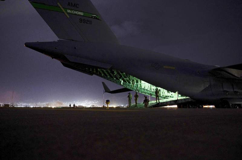 In this Aug. 30, 2021, photo provided by the U.S. Air Force, a Air Force aircrew, assigned to the 816th Expeditionary Airlift Squadron, prepares to receive soldiers, assigned to the 82nd Airborne Division, to board a U.S. Air Force C-17 Globemaster III aircraft in support of the final noncombatant evacuation operation missions at Hamid Karzai International Airport in Kabul Afghanistan. (Senior Airman Taylor Crul/U.S. Air Force via AP)