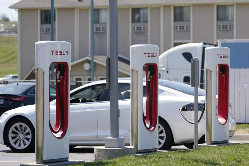 FILE - In this Monday, April 5, 2021 file photo, a Tesla electric vehicle charges at a station in Topeka, Kan. With strong sales of its electric cars and SUVs, Tesla on Monday, April 26, 2021 posted its seventh-straight profitable quarter. (AP Photo/Orlin Wagner)