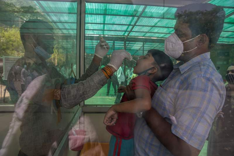 A health worker takes a swab sample of a child to test for COVID-19 at a government hospital in Noida, a suburb of New Delhi, India, Thursday, April 15, 2021. India reported more than 200,000 new coronavirus cases Thursday, skyrocketing past 14 million overall as an intensifying outbreak puts a grim weight on its fragile health care system. (AP Photo/Altaf Qadri)