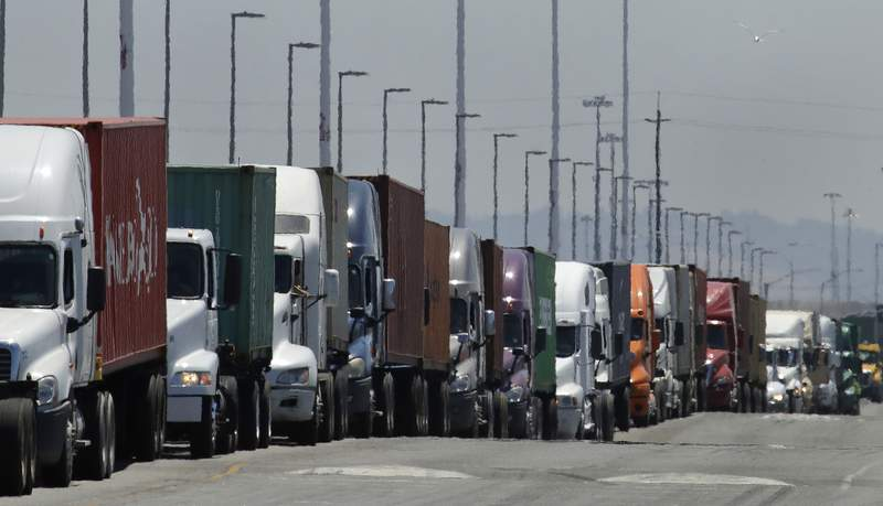FILE - In this July 22, 2019 photo, trucks hauling shipping containers wait to unload at the Port of Oakland in Oakland, Calif.  The Commerce Department issues its second estimate of how the U.S. economy performed in the first quarter of 2020 on Thursday, May 28, 2020.(AP Photo/Ben Margot, File)