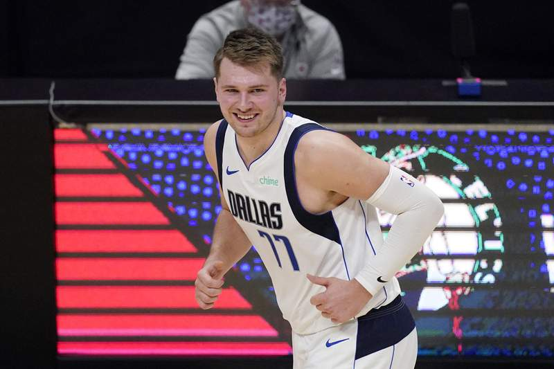 FILE - In this May 22, 2021, file photo, Dallas Mavericks guard Luka Doncic smiles after scoring during the first half in Game 1 of an NBA basketball first-round playoff series against the Los Angeles Clippers in Los Angeles. Doncic is set to sign a $207 million supermax extension with the Mavericks, who sent an entourage to the Slovenian star's home country to finish off the biggest contract in franchise history. (AP Photo/Mark J. Terrill, File)